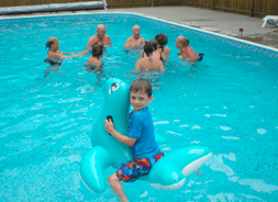 young boy on floatie in swimming pool with adults in the background